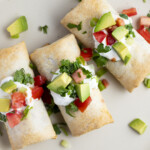 Frozen burritos cooked in the air fryer topped with pico, guacamole, and sour cream