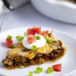 Slice of taco pie topped with sour cream and tomatoes on a white plate