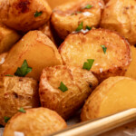 close up image of air fryer home fries with flakey sea salt and chopped parsley on top