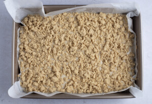 Top layer of vegan coffee cake in 9x13 baking dish with parchment paper