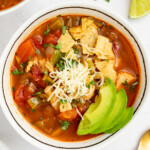 chili's southwest chicken soup in a bowl with crushed tortilla chips, cheese, and sliced avocado on top
